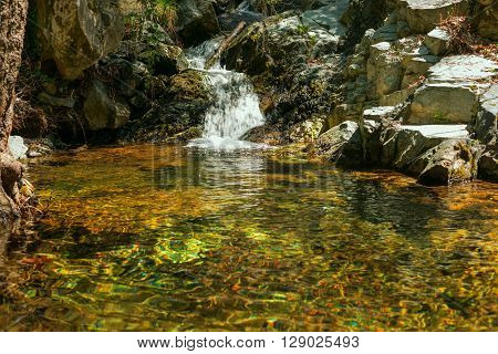 Small waterfall on the mountain river on a sunny morning not far from the waterfall Kalidonia Troodos Cyprus.