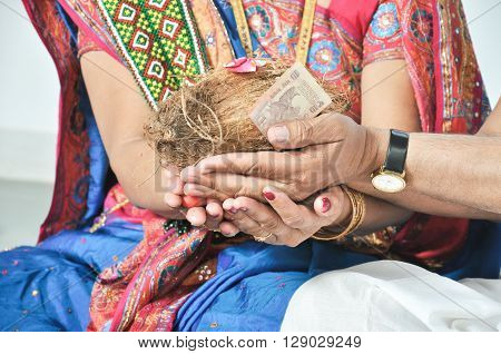 coconut and Indian ten rupee note on the Indian men and women hand