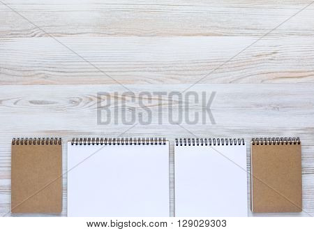 Soft Planked Wooden Board with Line of Notepads Opened and Folded in Warm Serene Color Tone
