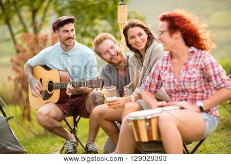 Cheerful boys and girls playing music instruments in camp in forest