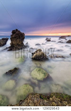Long exposure seascape during blue hour sunset with rocks as foreground. Shot taken Cadiz coast Spain.