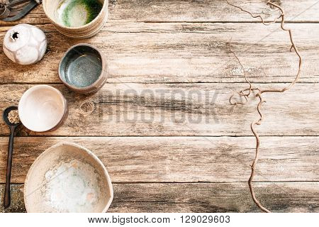 Flat lay set of handmade ceramic crockery. Top view of unusual creative bowls on  old wooden background. Beige empty ceramics over wooden table with free space