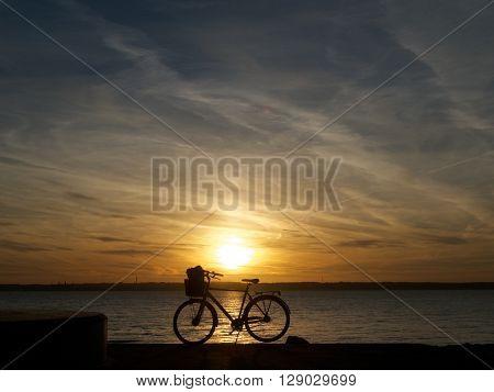 Cykel parkerad vid stranden i den vackra solnedgången.