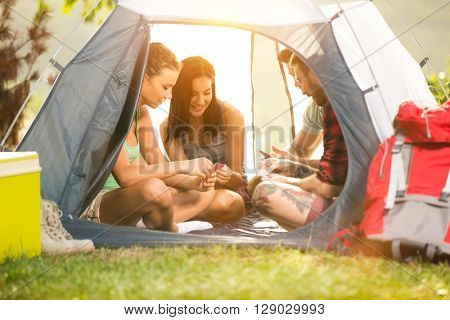 Happy fiends in tent having fun on camping trip enjoy in vacation together