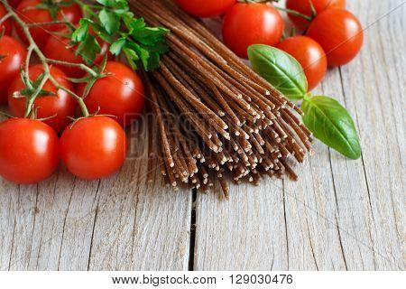 Wholegrain rye spaghetti tomatoes and herbs on wood