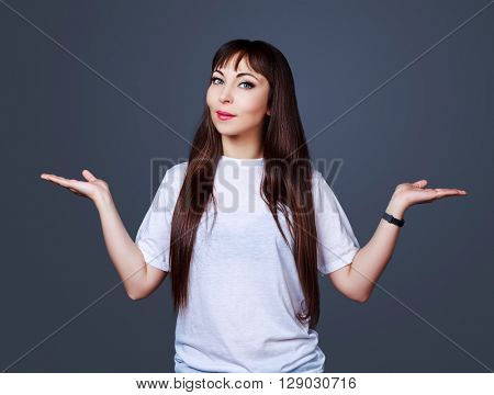 smiling brunette woman with her hands up, place your product here, isolated against gray studio background