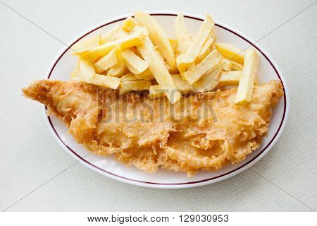 Traditional english meal - deep fried fish cod with chips served in local restaurant in Hastings England.