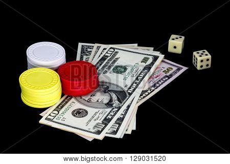 Gambling chips money and dice isolated against a black background