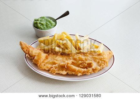 Traditional english meal - deep fried fish cod with chips and mashed green peas served in local restaurant in Hastings England.