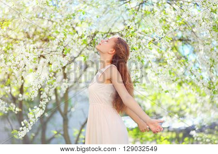 Beautiful Young Woman Enjoying Smell In Flowering Spring Garden