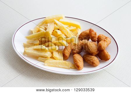 Traditional english meal - deep fried seafood scampi with chips served in local restaurant in Hastings England.