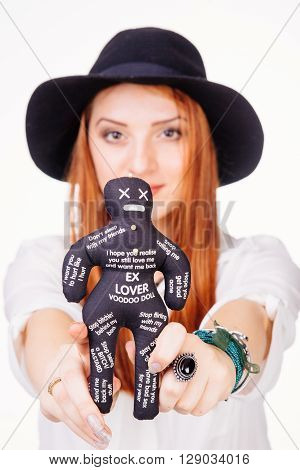 Portrait of a young woman holding an ex lover voodoo doll - isolated on white.