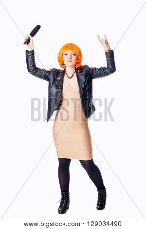 Pose of a rocker singer woman with a microphone showing rock sign - isolated on white.