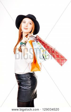 Young woman holding shopping bags and looking away - isolated on white.