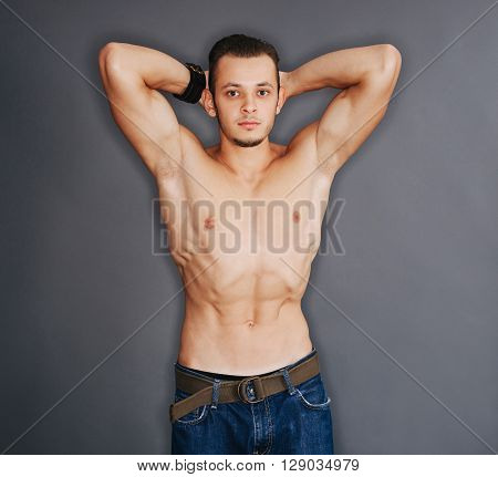 Closeup of bodybuilder with arms around his head