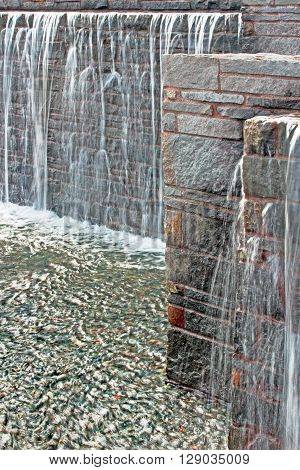 Waterfall from a fountain cascading over brickwork vertical format.