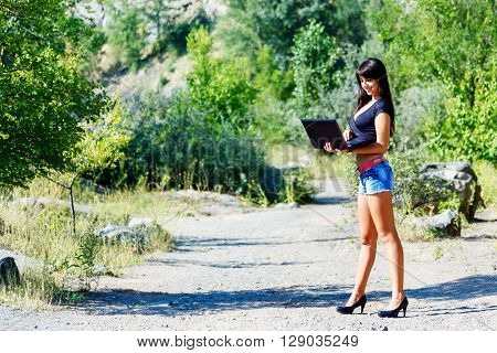 beautiful smiling brunette woman working with a laptop among the greenery and stones. Student or businesswoman