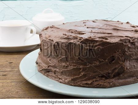 Chocolate cake close up on blue plate on rustic wood table with tea cup