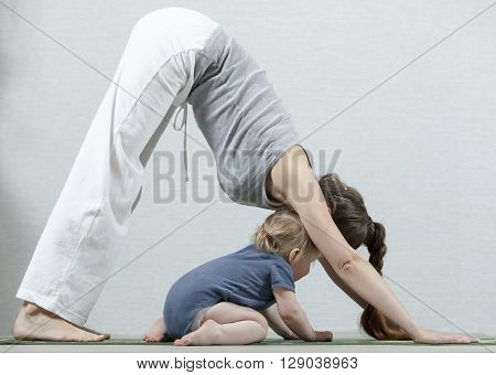 Hatha yoga fitness young athletes mother with baby