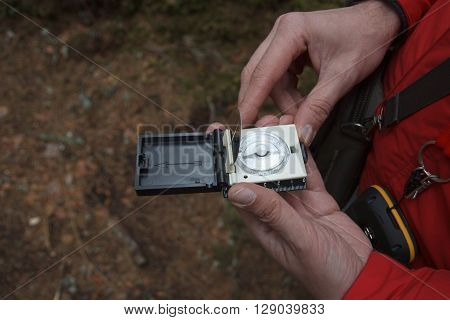 A man using a compass in a forest