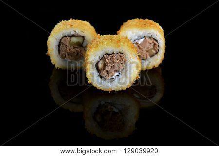 three fresh and tasty sushi rolls on black