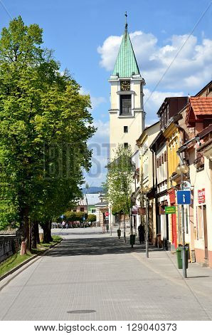 Bytca, Slovakia - April 30 2016: View at the street with green trees houses and christian Church of all saints