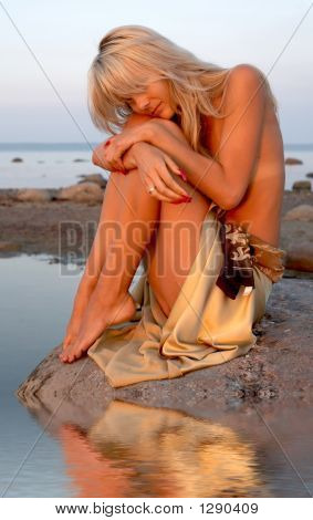 Girl Sitting On The Rock With Water Reflection