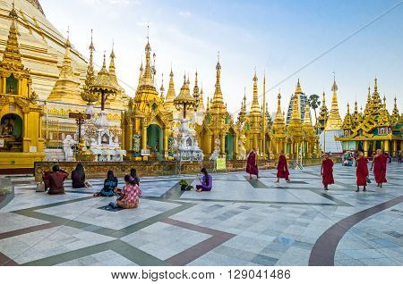 Yangon Myanmar - January 9 2012: Religious in prayer and monks in the Swedagon Pagoda.