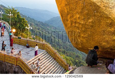 Kyaikhto Myanmar - January 10 2012: Religious in prayer under the delicately balanced golden Stupa on the sacred Buddhist mountain