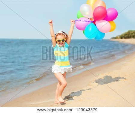 Happy Smiling Child On Beach Playing With Colorful Balloons Near Sea Summer Day