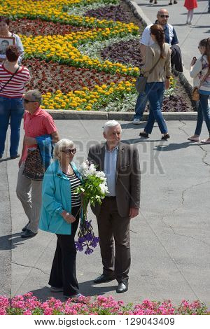 Senior Couple Is Standing With Flowers Near Flower Bed.