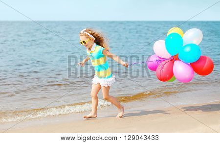 Happy Smiling Child Playing On Beach Running With Colorful Balloons Over Sea