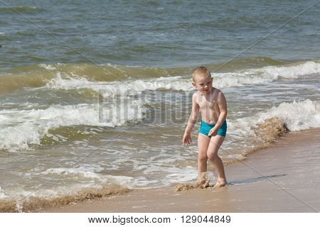 the little boy in blue swimming trunks has a good time at the sea