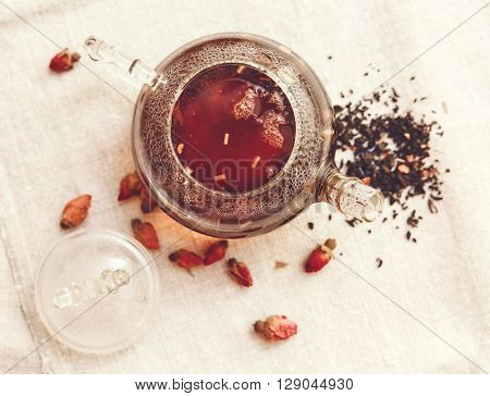 The Dry Red Small Roses with Black Tea in the Glass Teapot,Tea Drinking,Aromatized FlowersTable Rough Linen Tableclose;Toned,top view