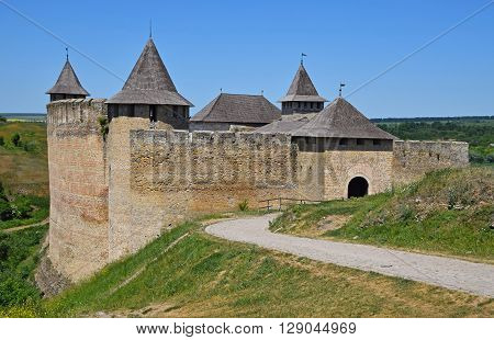 Medieval old fortress castle with ancient stone walls wooden roofs and road green hills and clear blue sky Khotyn Ukraine