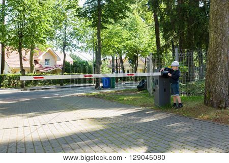 the little boy operates a barrier and blocks the road