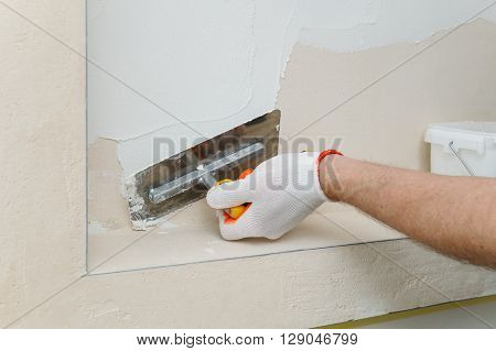 Decorative plaster coating. Man puts plaster on the wall.