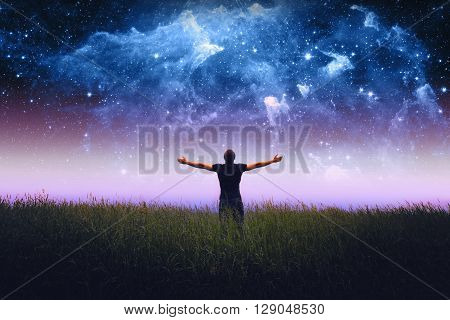 silhouette of man standing in a field. Elements of this image furnished by NASA.