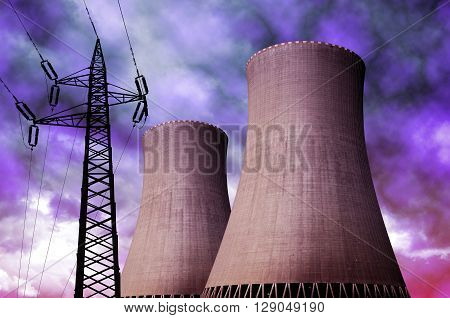 Nuclear power plant with electricity pylon against storm clouds