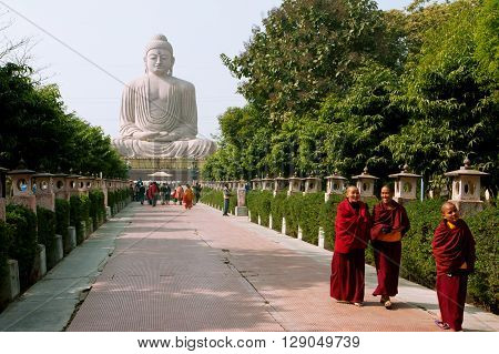 BODHGAYA, INDIA - JAN 8, 2013: Group of Buddhist monks walking on the alley from the huge statue of Buddha on January 8, 2013 in Bodhgaya India. Siddhartha Gautama attained enlightenment here at 500 BC.