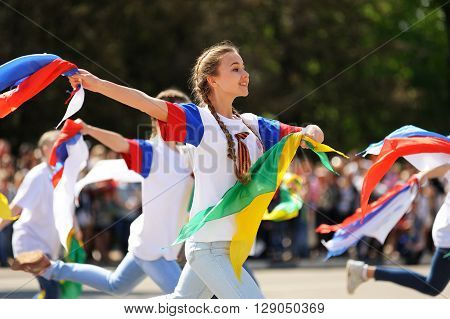 Orel Russia - May 9 2016: Celebration of 71th anniversary of the Victory Day (WWII). Girls in white dancing with colored ribbons outdoors closeup