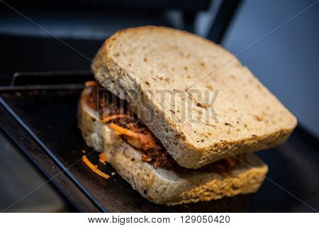 Wholemeal toasted bread sandwich with meat and vegetables in a toaster in a cafe