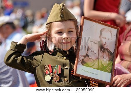 Orel Russia - May 9 2016: Celebration of 71th anniversary of the Victory Day (WWII). Girl in military uniform with medals carrying soldier's portrait closeup