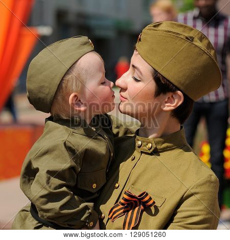 Orel Russia - May 9 2016: Celebration of 71th anniversary of the Victory Day (WWII). Woman with child in soviet military uniform with St.George ribbon closeup