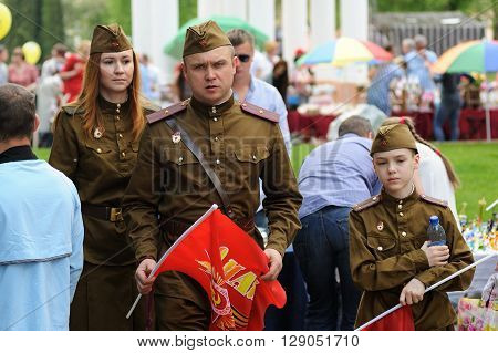 Orel Russia - May 9 2016: Celebration of 71th anniversary of the Victory Day (WWII). Family in soviet military uniform with red flags closeup