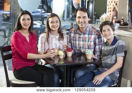 Smiling Family With Ice Creams At Table In Parlor