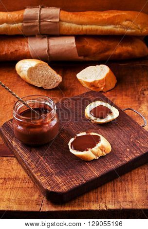 Appetizer set with freshly baked French baguette and chocolate ganache on a rustic table