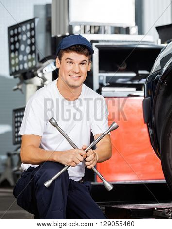 Confident Mechanic Holding Rim Wrench At Garage