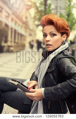 Young woman on a street bench with tablet computer. Young beautiful woman sitting on a bench on the street with tablet computer