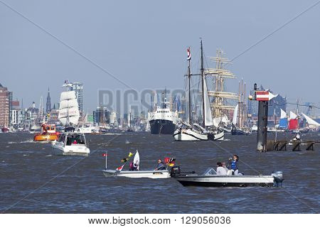 Hamburg, Germany - May 8, 2016: Variety of sailing ships and other vessels at departure parade of 827th Hamburg Port Anniversary, small boats with spectators in foreground.